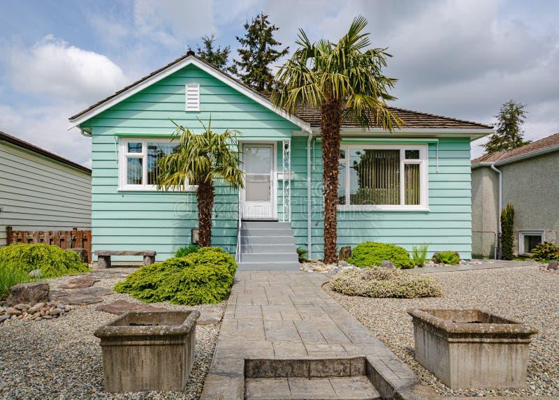 Odnawi?cy rodzina dom z dekoracyjnymi drzewkami palmowymi przy wej?ciem obrazy stock