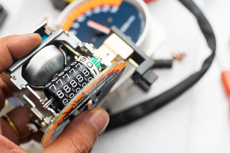 """Odometer Reprogramming """"car clocking"""" hand of technician Mod. Odometer Reprogramming """"car clocking"""" hand of technician royalty free stock photography"""