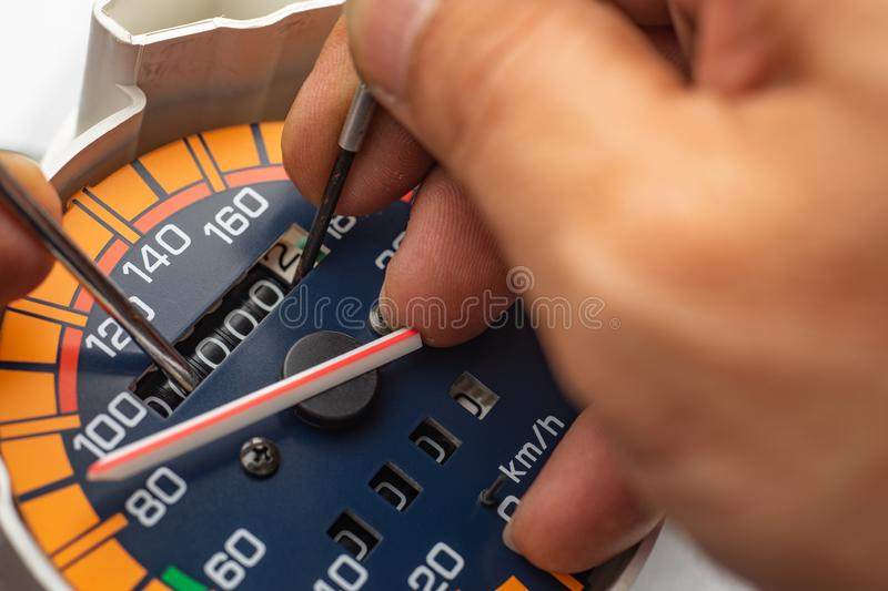 """Odometer Reprogramming """"car clocking"""" hand of technician Mod. Ify The speedometer and reset number to zero stock photo"""
