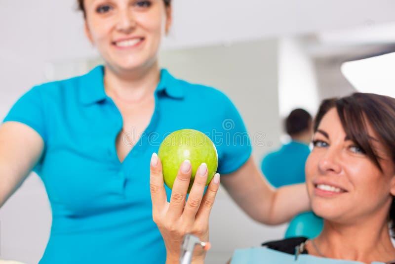 Odontoiatria, denti sani Il dentista dà la mela verde ad una bella ragazza, un paziente per controllare i denti Denti difficili fotografie stock libere da diritti