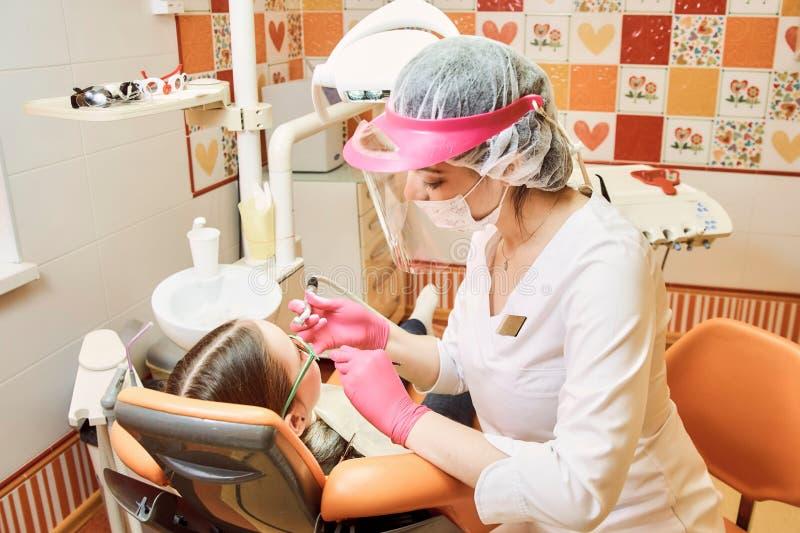 Odontoiatria pediatrica Il dentista tratta i denti della bambina immagine stock