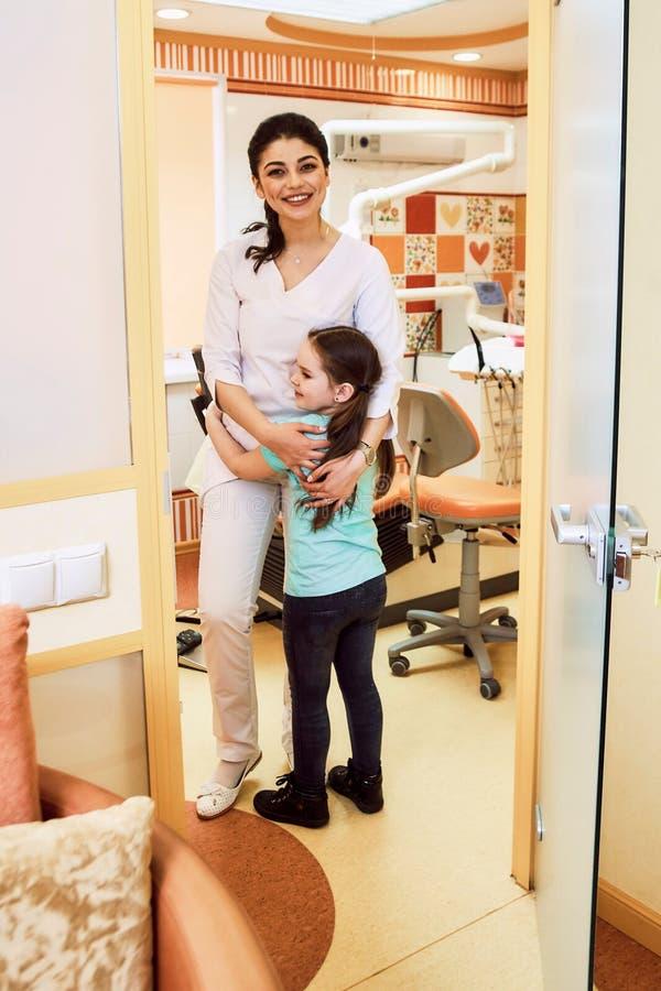 Odontologia pediatra A menina está feliz encontrar o dentista foto de stock