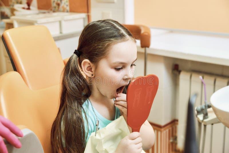 Odontologia pediatra A menina olha seus dentes no espelho fotos de stock royalty free