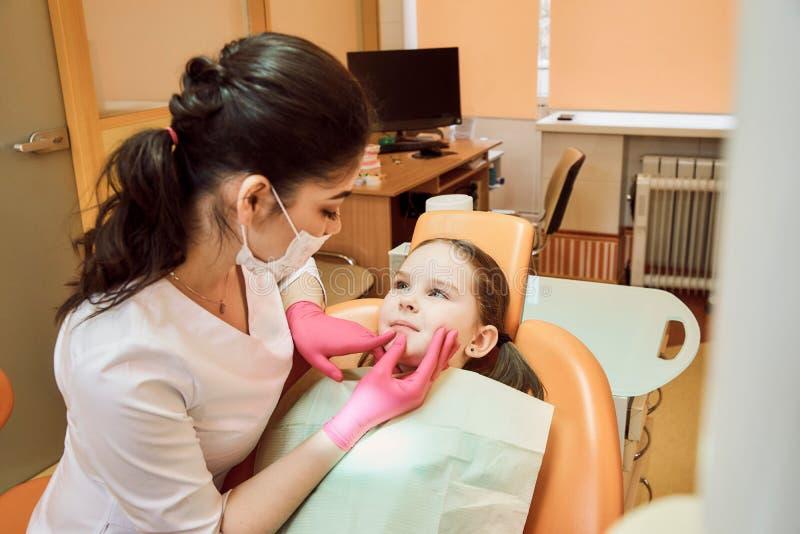 Odontologia pediatra O dentista trata os dentes da menina fotografia de stock
