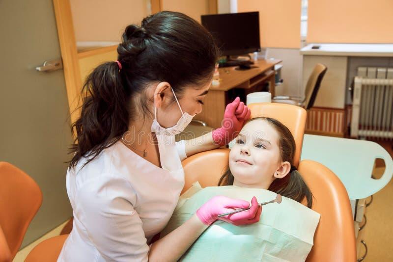 Odontologia pediatra O dentista trata os dentes da menina imagem de stock royalty free