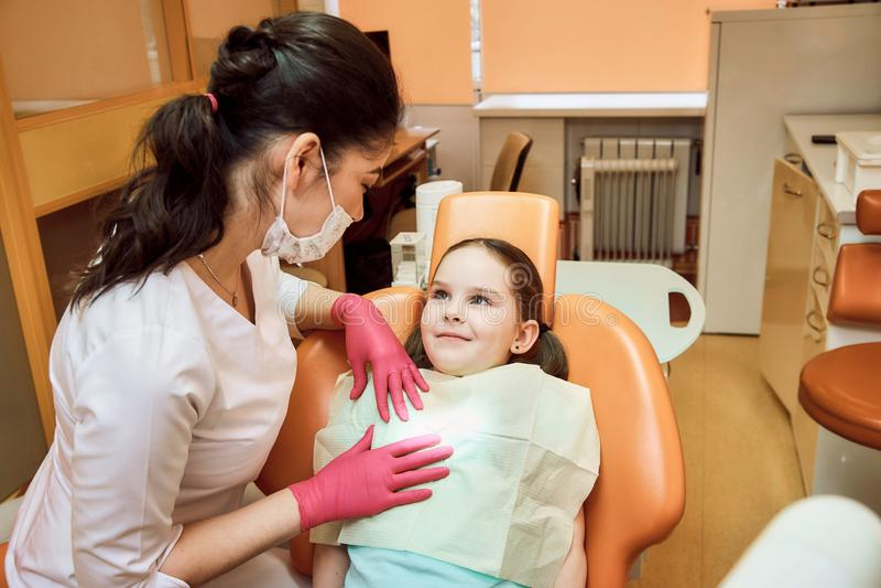 Odontologia pediatra O dentista trata os dentes da menina foto de stock