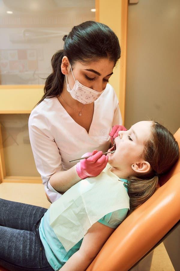 Odontologia pediatra O dentista trata os dentes da menina imagens de stock royalty free