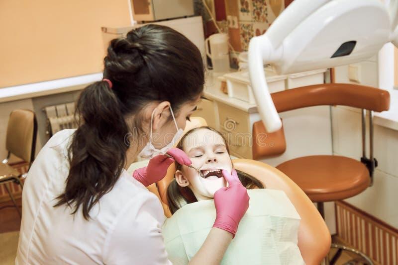 Odontologia pediatra O dentista trata os dentes da menina fotografia de stock royalty free