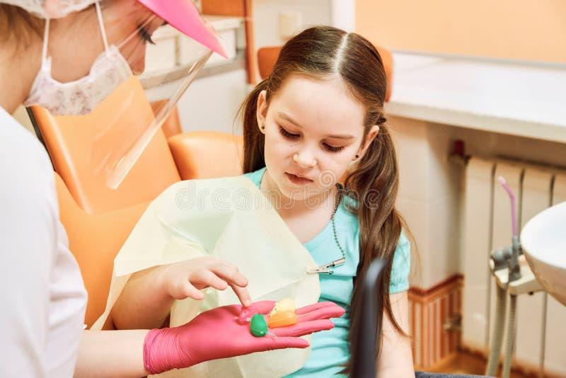 Odontologia pediatra O dentista trata os dentes da menina imagens de stock