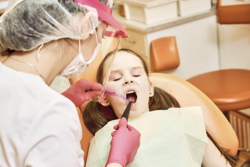 Odontologia pediatra O dentista trata os dentes da menina imagem de stock