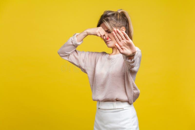 Odore puzzolente Ritratto di una giovane donna insoddisfatta con capelli biondi in camicetta di beige, isolata su fondo giallo immagine stock libera da diritti