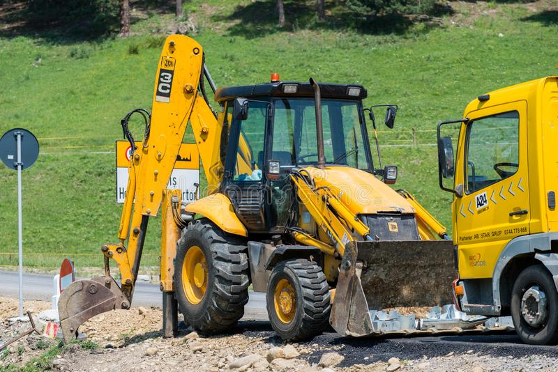 Jcb  excavator  near  road construction site at  summertime. Odorheiu Secuiesc, Romania- 16 June 2019: Jcb  excavator  near  road construction site at royalty free stock photo