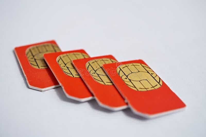 Odosobniona grupa cztery czerwonej SIM karty używać w telefonach komórkowych z ostrością na złotym mikro układzie scalonym (telef obraz stock