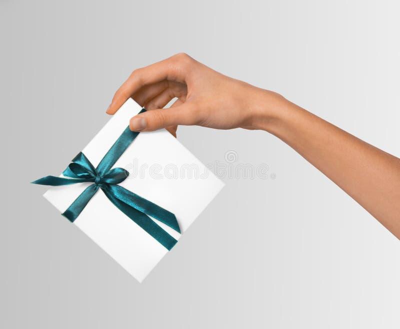 Odosobnione kobiet ręki trzyma wakacje Teraźniejszego Białego pudełko z Błękitnym faborkiem na Białym tle zdjęcia stock
