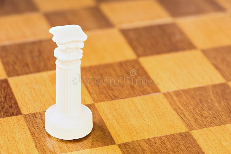 Odosobniony biały szachowy gawron kamień lub klingeryt na kwadratowej drewno desce fotografia stock