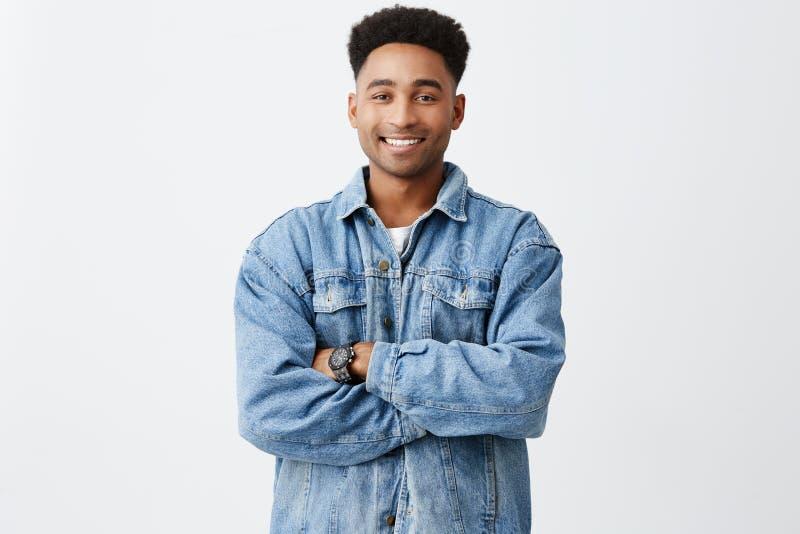 Odosobniony portret młody śmieszny ciemnoskóry mężczyzna z rękami krzyżował z afro fryzurą w przypadkowej białej koszula zdjęcia stock