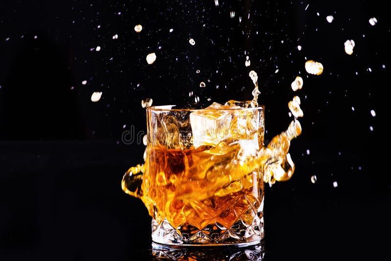 Odosobniony strza? whisky z plu?ni?ciem na czarnym tle, brandy w szkle zdjęcia stock