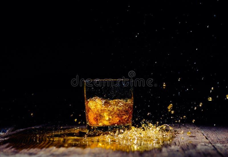 Odosobniony strzał whisky z pluśnięciem na drewnianym tle zdjęcia stock
