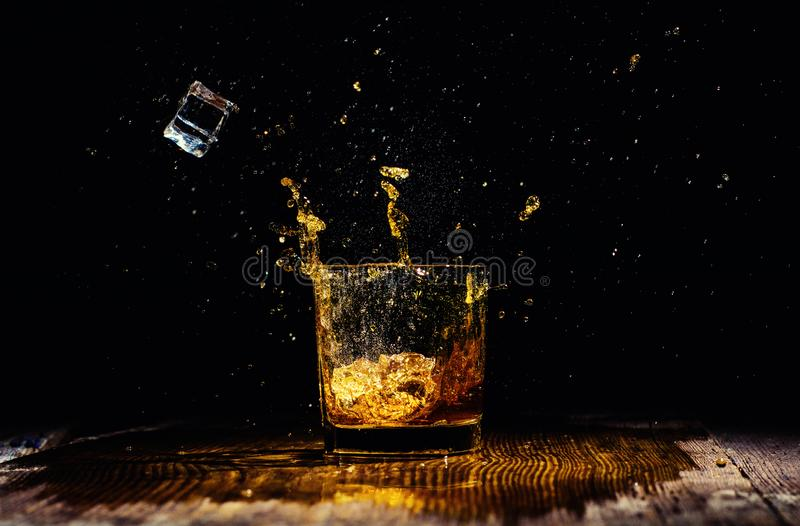 Odosobniony strza? whisky z plu?ni?ciem na czarnym tle obrazy stock