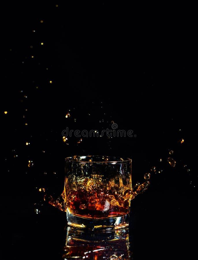 Odosobniony strza? whisky z plu?ni?ciem na czarnym tle zdjęcia royalty free