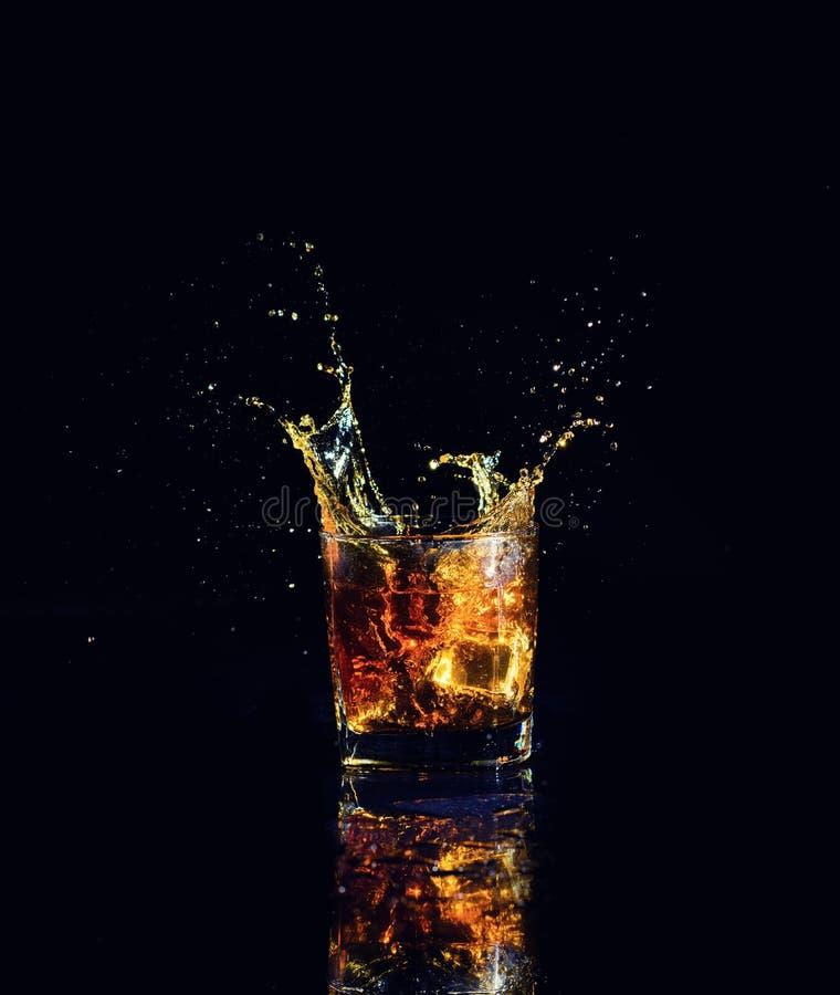 Odosobniony strza? whisky z plu?ni?ciem na czarnym tle obraz royalty free
