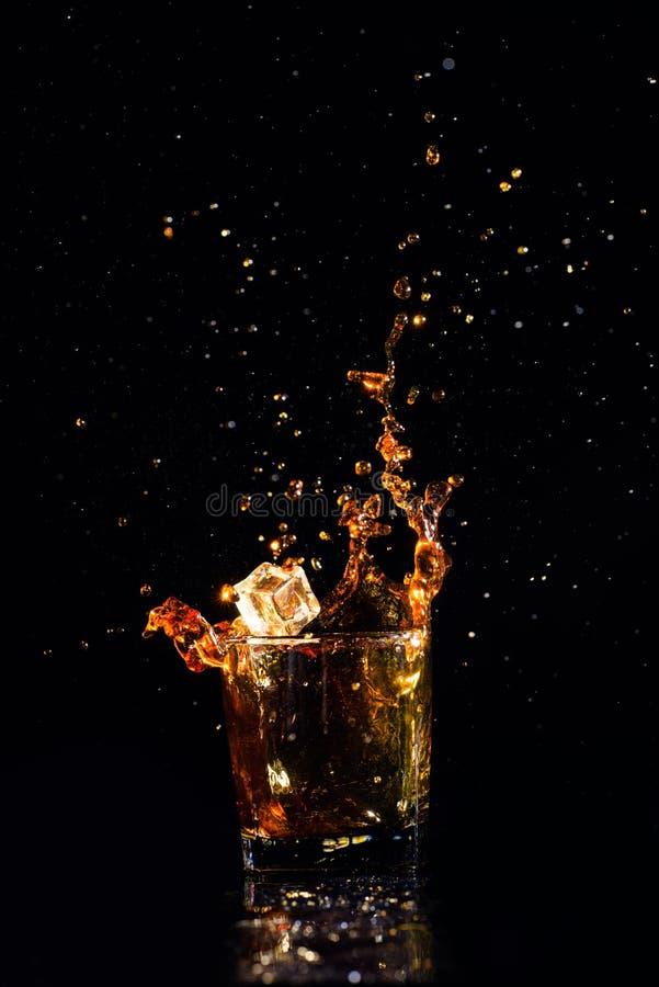 Odosobniony strza? whisky z plu?ni?ciem na czarnym tle zdjęcie royalty free