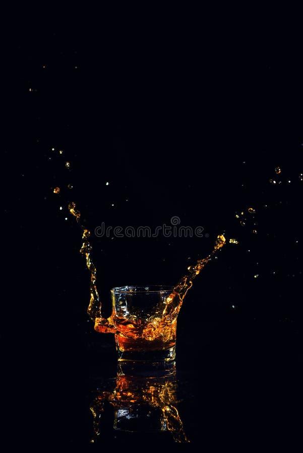 Odosobniony strza? whisky z plu?ni?ciem na czarnym tle fotografia stock