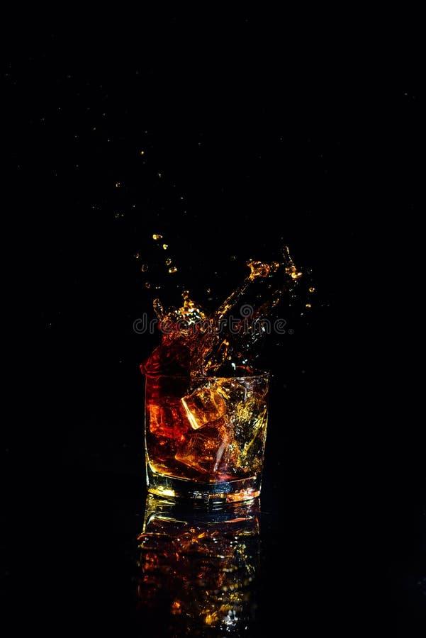 Odosobniony strza? whisky z plu?ni?ciem na czarnym tle zdjęcie stock