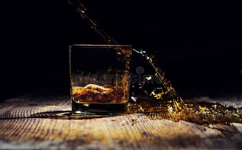 Odosobniony strza? whisky z plu?ni?ciem na czarnym tle obrazy royalty free
