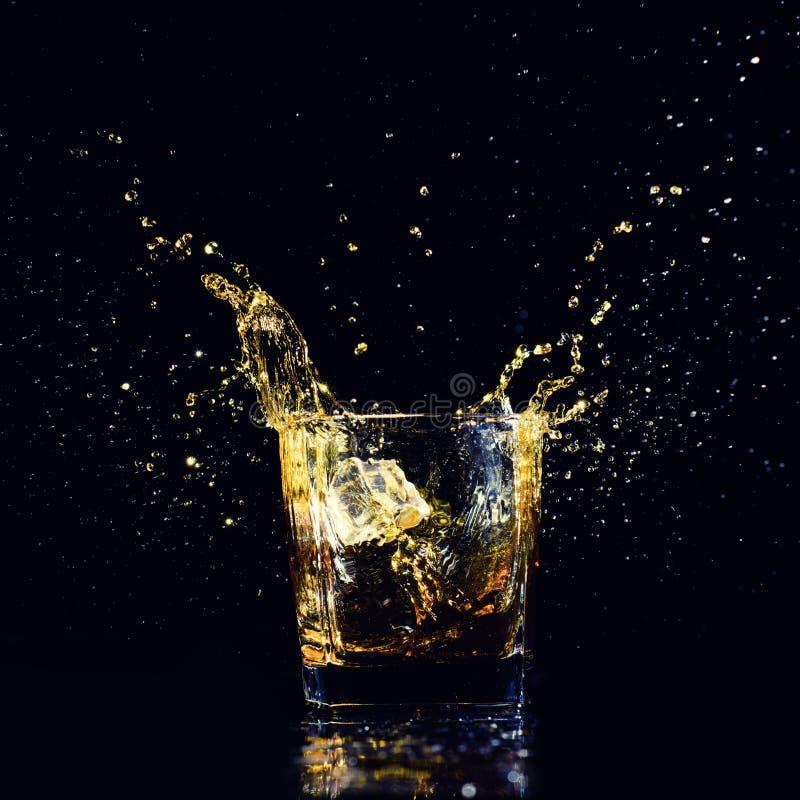 Odosobniony strza? whisky z plu?ni?ciem na czarnym tle obraz stock