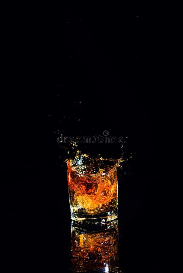 Odosobniony strza? whisky z plu?ni?ciem na czarnym tle zdjęcia stock