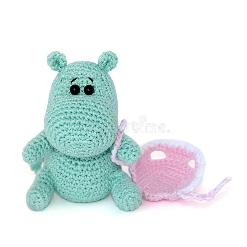 Odosobniony szydełkujący amigurumi zabawki mały turkusowy hipopotam z smutnym zdziwionym spojrzeniem siedzi, trzyma, białą nakręt obraz royalty free