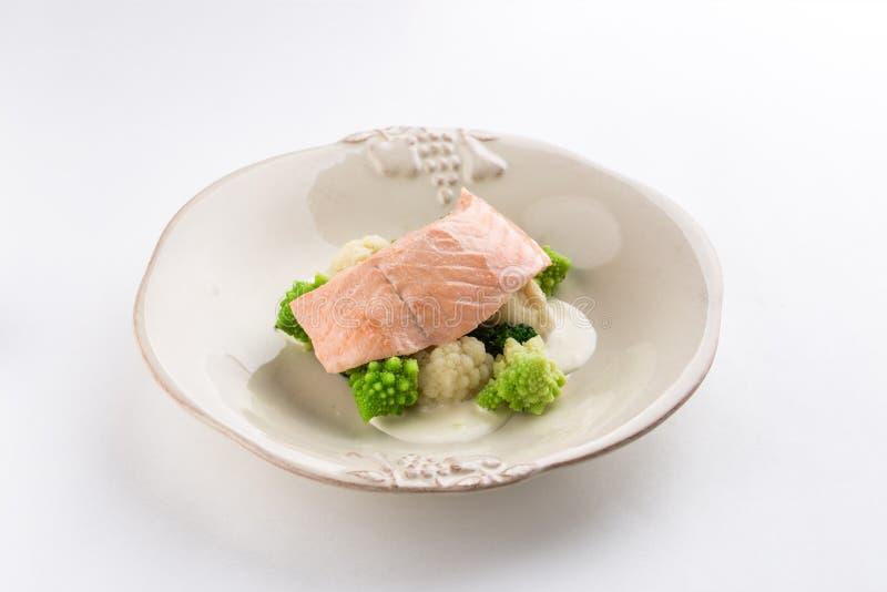 Odparowany łosoś, kalafior i brokuły na bielu talerzu odizolowywającym na białym tle, fotografia royalty free