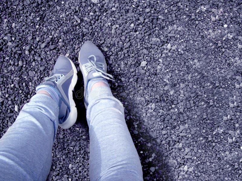 Odpoczynek po Jogging Kobiet nogi w szarych sneakers i szarzy sweatpants przeciw otoczakom fotografia stock
