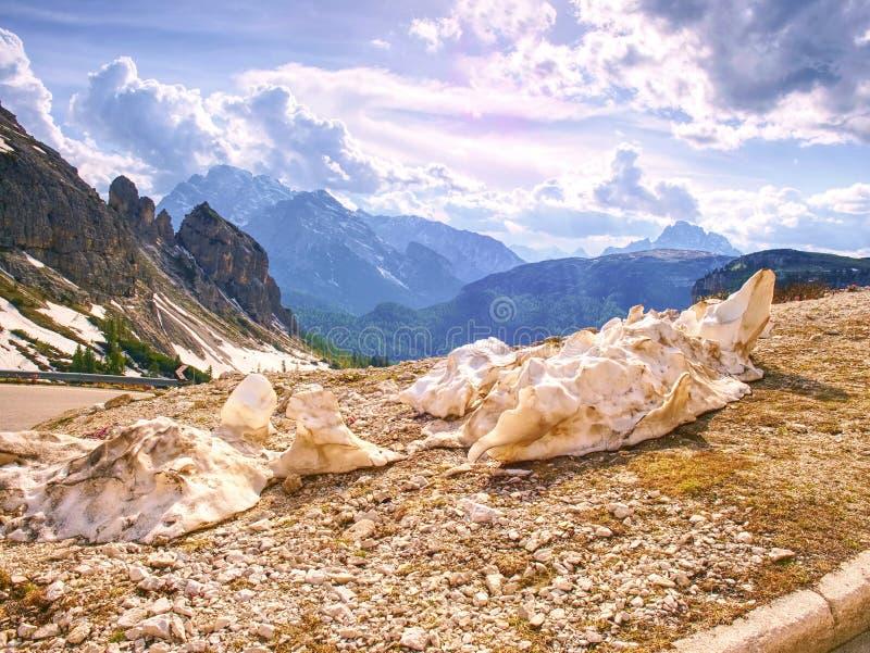 Odpoczynek roztapiający śnieg przy żwir drogą w wiosen górach zdjęcia stock