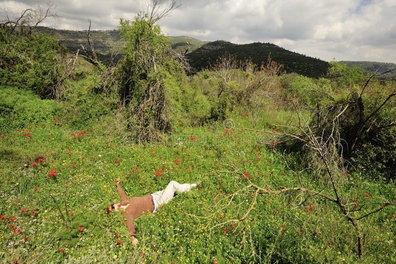 Odpoczynkowa kobieta w kwitnącej trawie obrazy stock