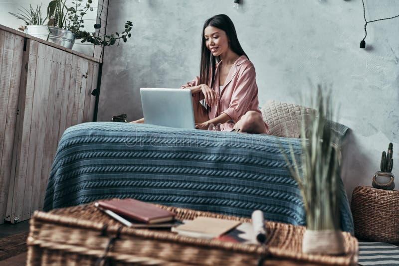 odpoczywa w domu Atrakcyjna młoda kobieta używa komputer i smili zdjęcia royalty free