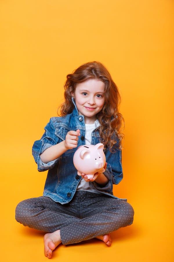 Odpowiedzialny dziewczyny kładzenia pieniądze w prosiątko banka dla przyszłościowego oszczędzania obraz stock