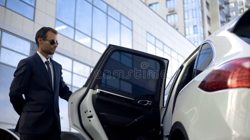 Odpowiedzialny kierowca otwiera samochodowego drzwi dla jego szefa, luksus usługa, obowiązki fotografia stock