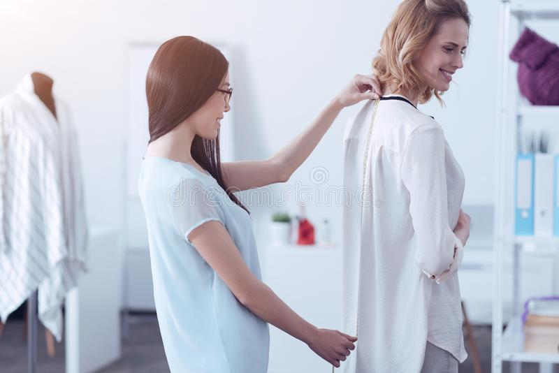 Odpowiedzialny krawczyna mierzy plecy jej klient zdjęcie royalty free