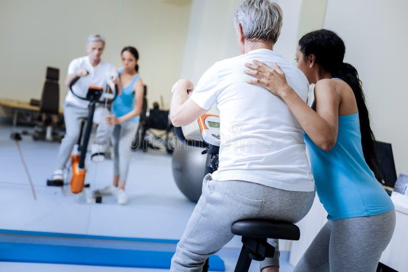 Odpowiedzialny trener pomaga jej pacjenta z ćwiczenie rowerem zdjęcia stock