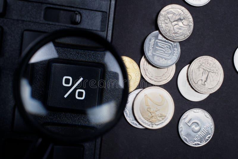 Odsetka znak przez magnifier i monet fotografia royalty free