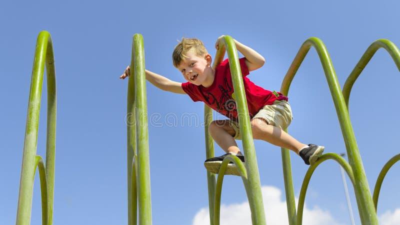 Odważna młoda chłopiec cimbing na playframe obraz royalty free