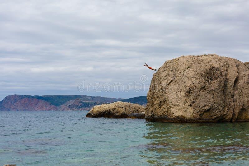 Odważny mężczyzna Skacze Od Wysokiej falezy skały W wodę morze fotografia royalty free