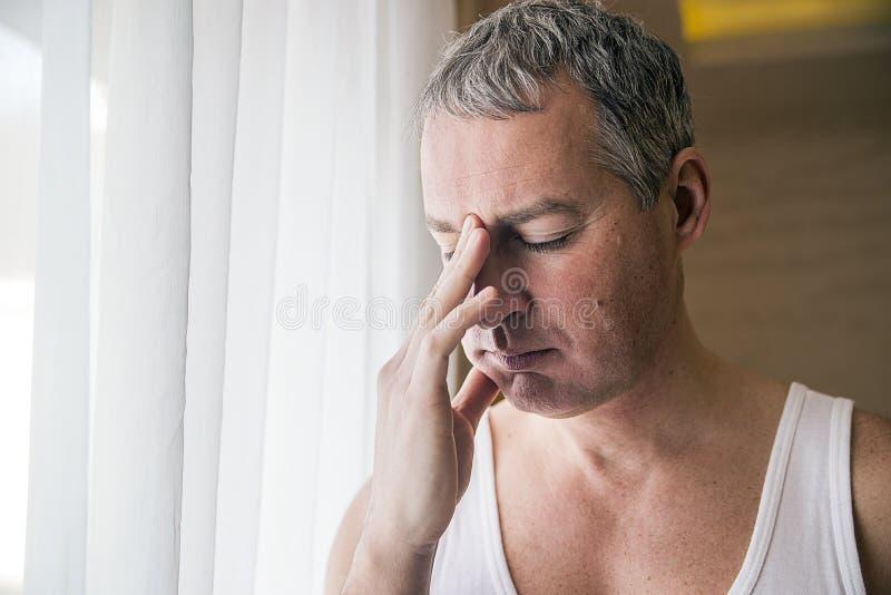 Odważny wieka średniego mężczyzna patrzeje nadokiennego, Smutny, i depresse zdjęcia royalty free