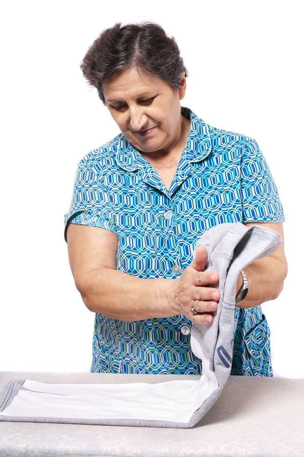 odzieżowa falcowania seniora kobieta obraz stock