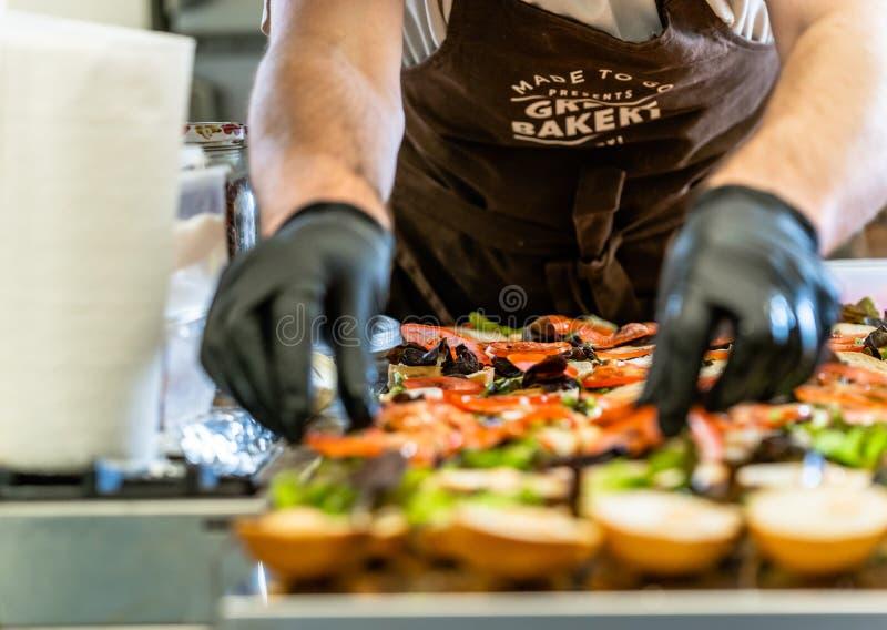 Odziena/Lettland - 24. August 2018: Männlicher Chef Putting Ingredients von Burgern in den schwarzen Handschuhen - Konzept von de lizenzfreies stockfoto