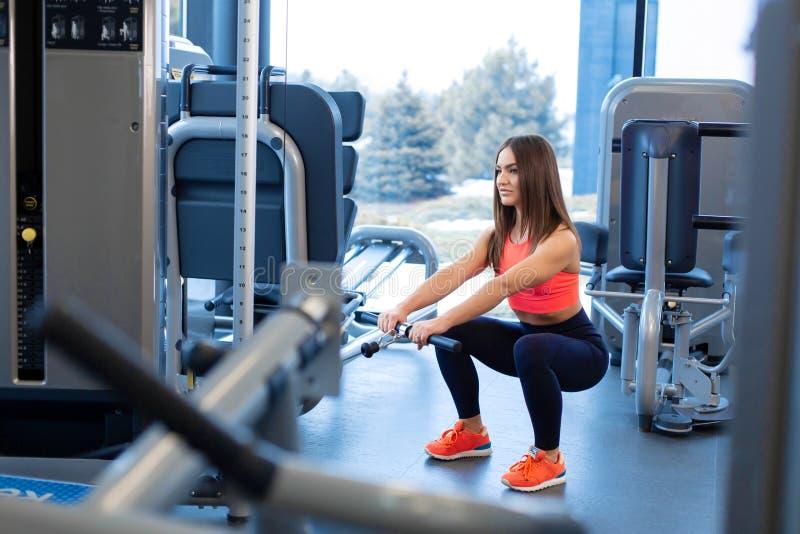 Oefeningen in de bloksimulator Biceps-uitbreiding Atletische vrouw werkt in gym royalty-vrije stock foto's