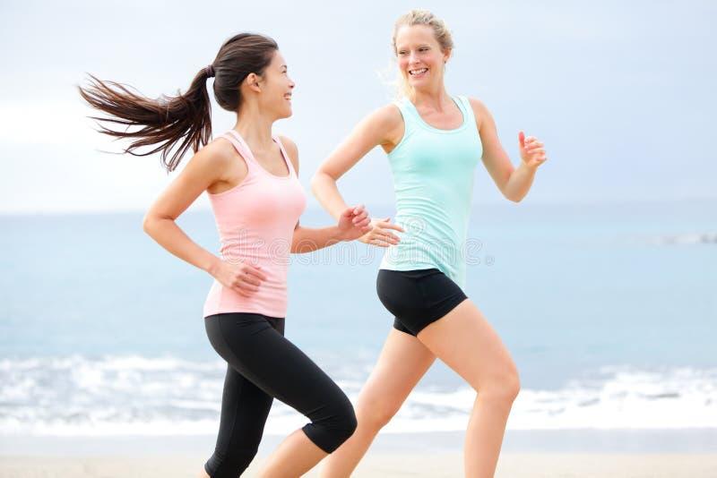 Oefenings het lopende vrouwen aanstoten gelukkig op strand royalty-vrije stock afbeeldingen