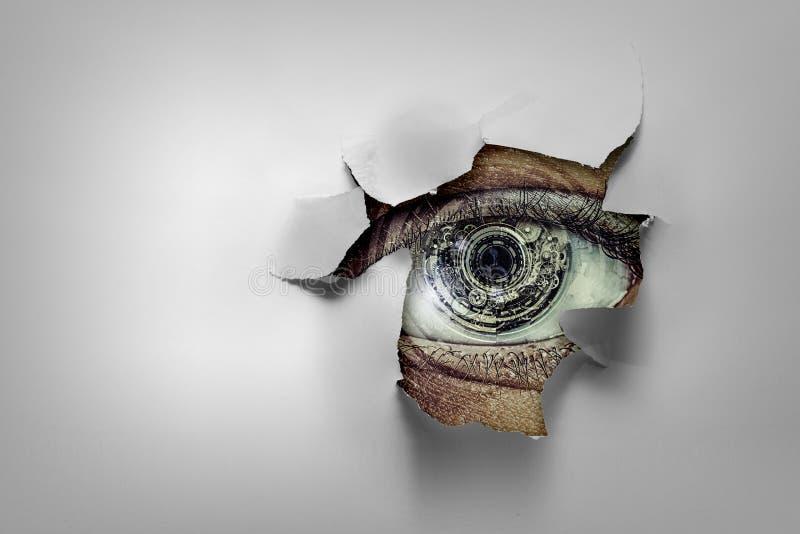 Oeil dans un trou de papier d?chir? image stock